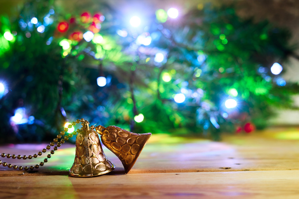 Golden Xmas bells over decorated Christmas background