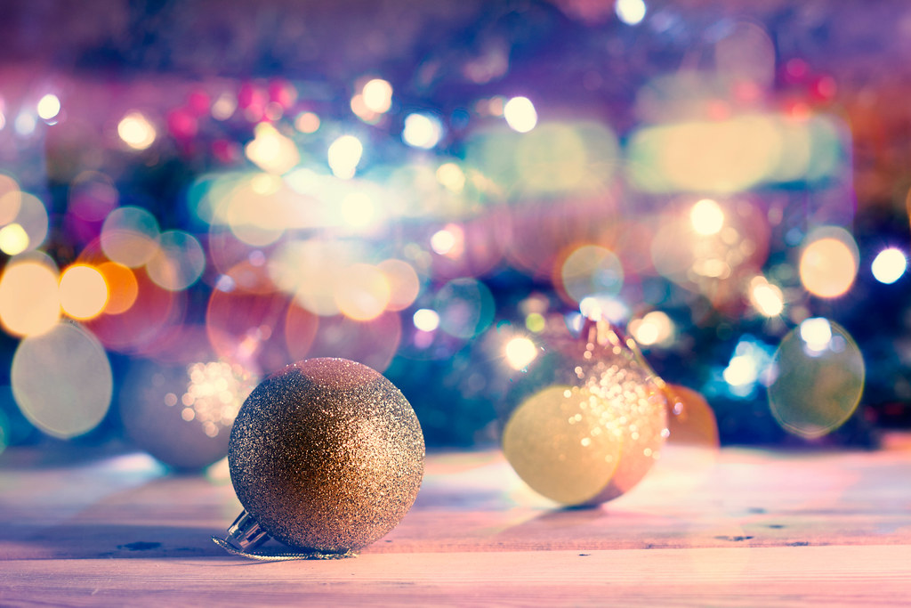 Golden Xmas decorative balls against Christmas background with bokeh lights