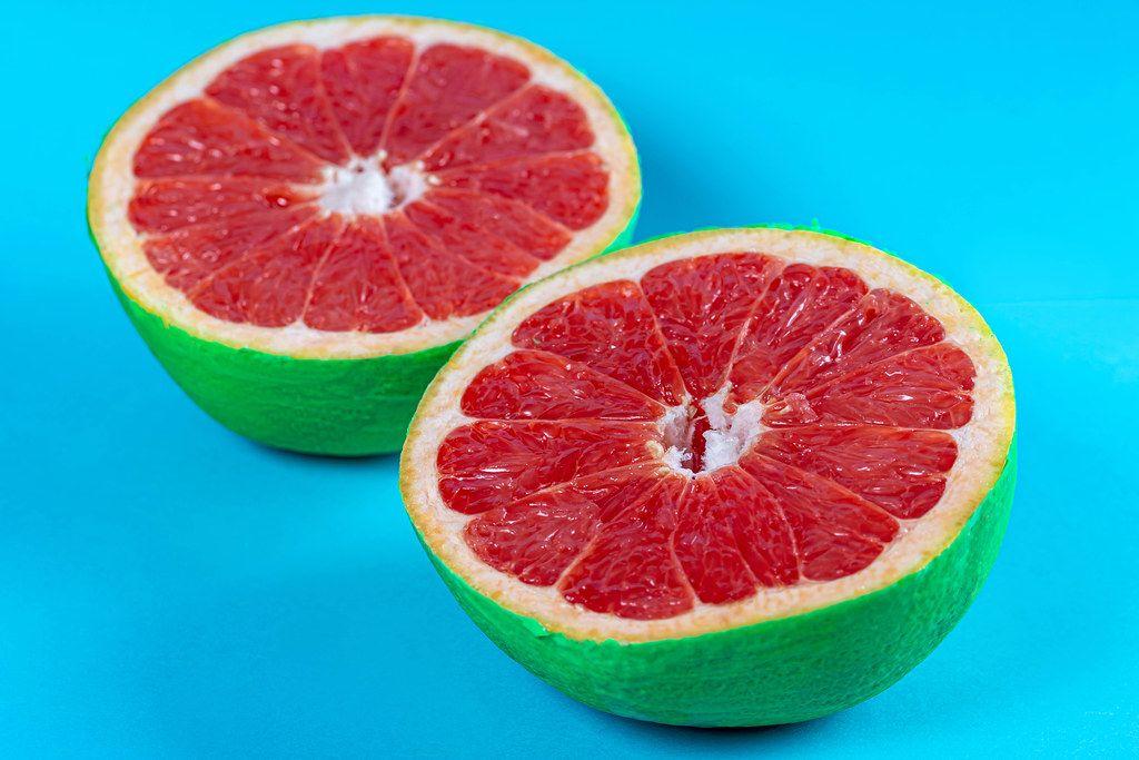 Grapefruit halves on pastel blue background. Summer concept