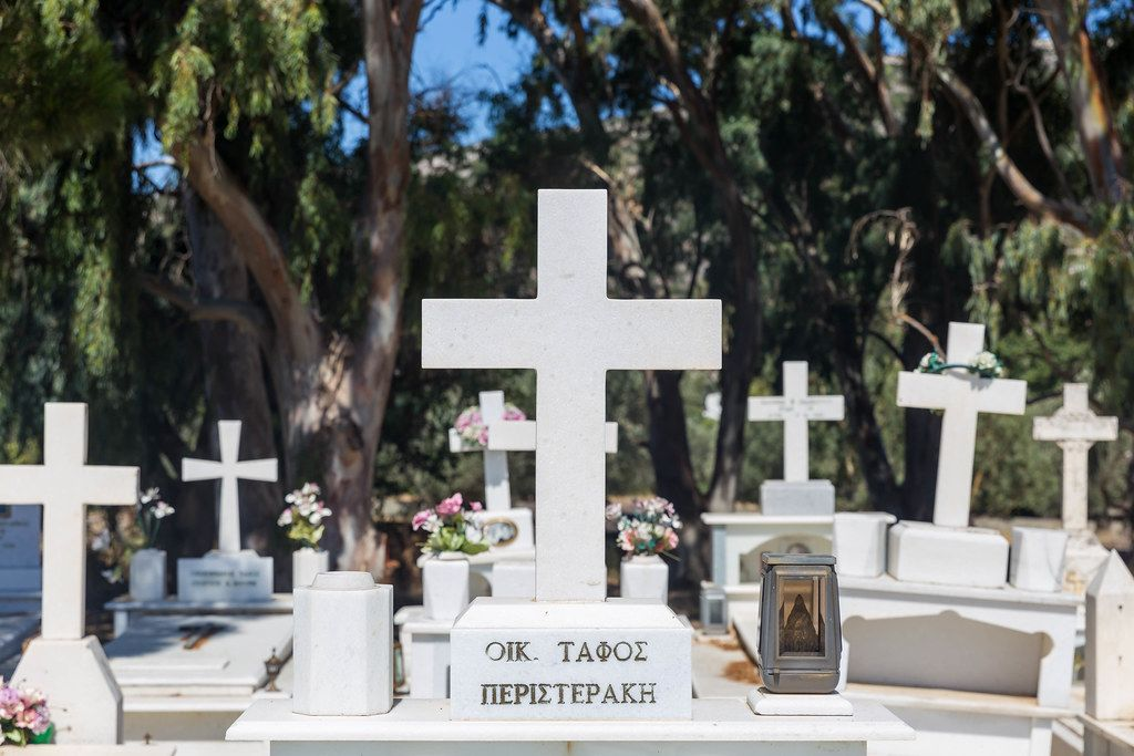 Graves with white marble crosses, flowers and Greek family name. Cemetery of Agios Charalampos, Naxos