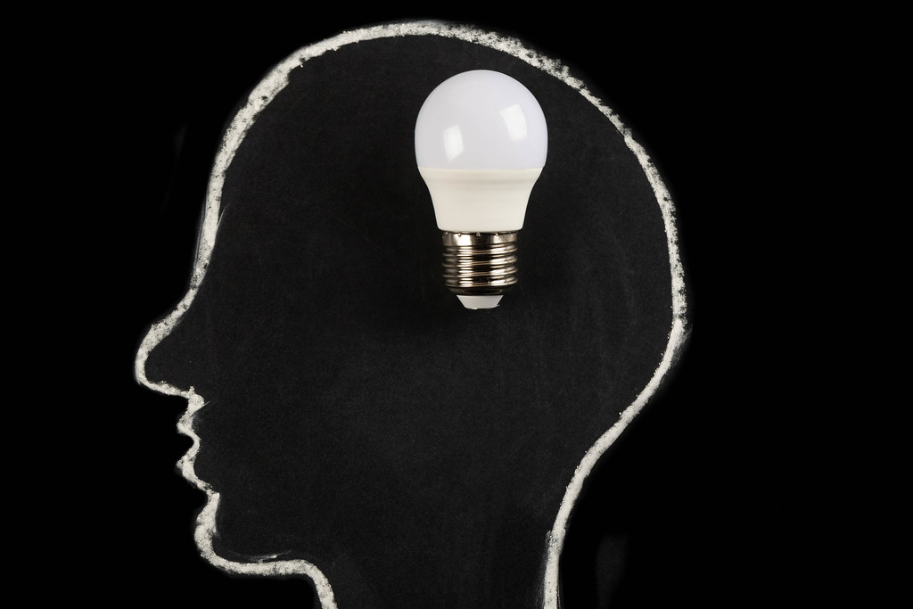 Great idea, finding solution concept, head silhouette with light bulb on dark background