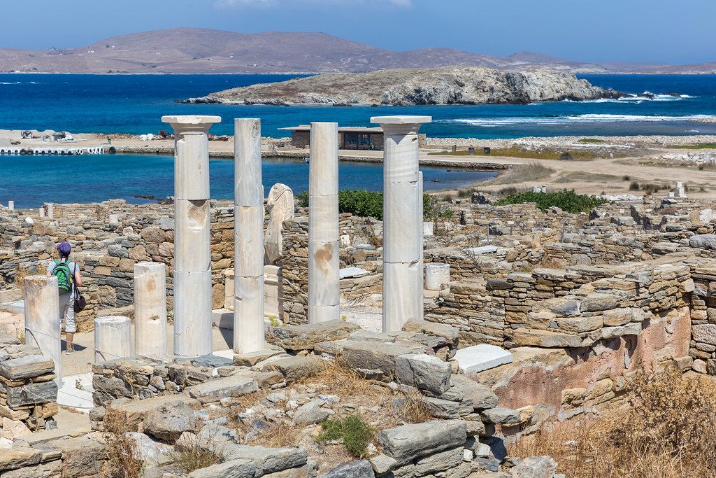 Greek columns of the House of Cleopatra in Delos. Uninhabited islands in the background