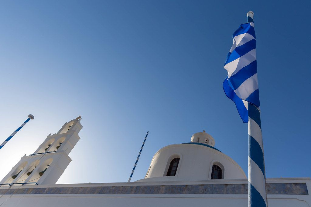 Greek flag wrapped on a white and blue mast with white church bells and blue dome in the background