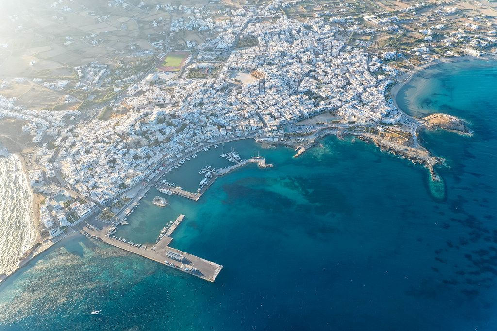 Greek islands: aerial view of the city of Naxos (Chora), its port and the beach of Agios Georgios