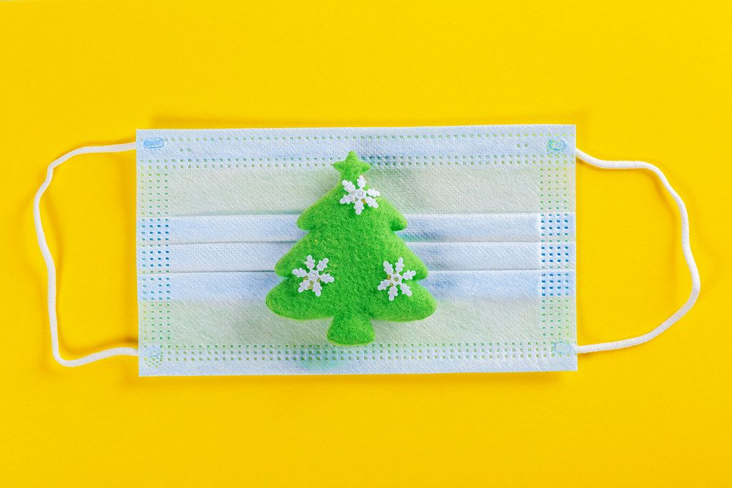 Green christmas tree toy with medical mask on yellow background