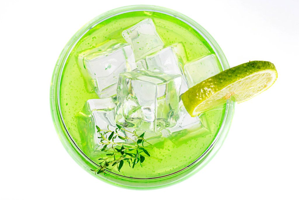 Green cocktail glass with ice cubes on white, top view