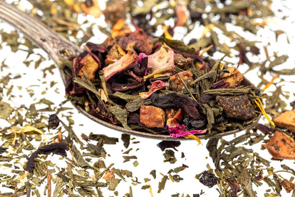 Green dry tea with dried fruits and petals in a spoon