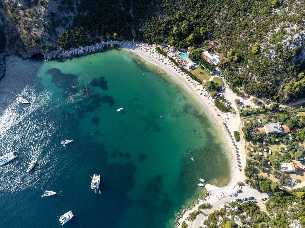 Green nature embraces the bay of Limnonari with sandy beach and shallow waters. Drone pic