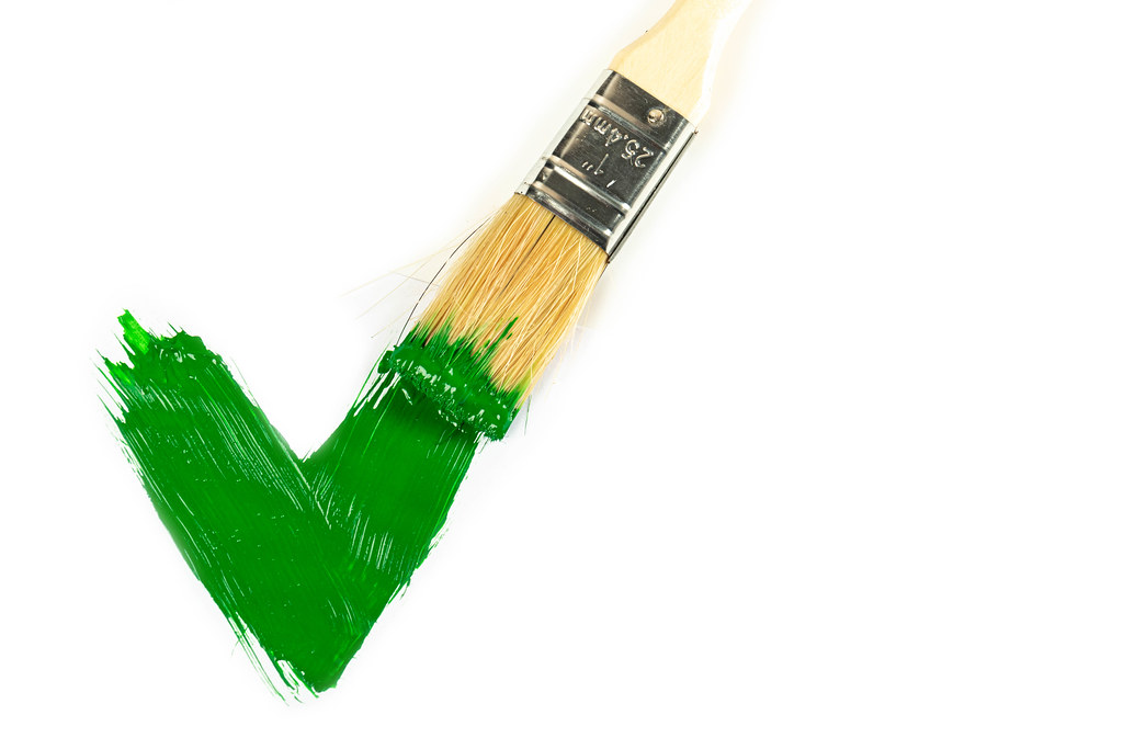 Green paint painted checkmark on white with a brush