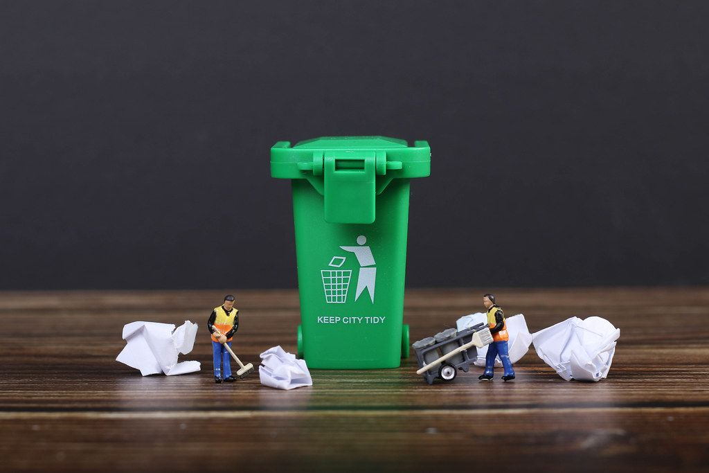 Green recycle bin with screwed up paper and tiny  cleaning workers