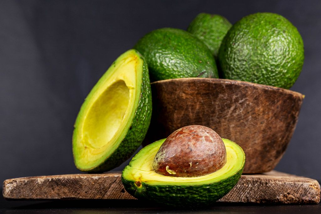 Green ripe avocado in a wooden bowl on a dark background