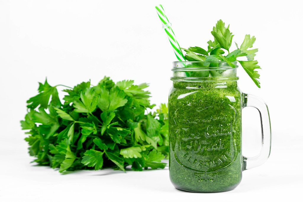 Green smoothie with fresh parsley on a white background