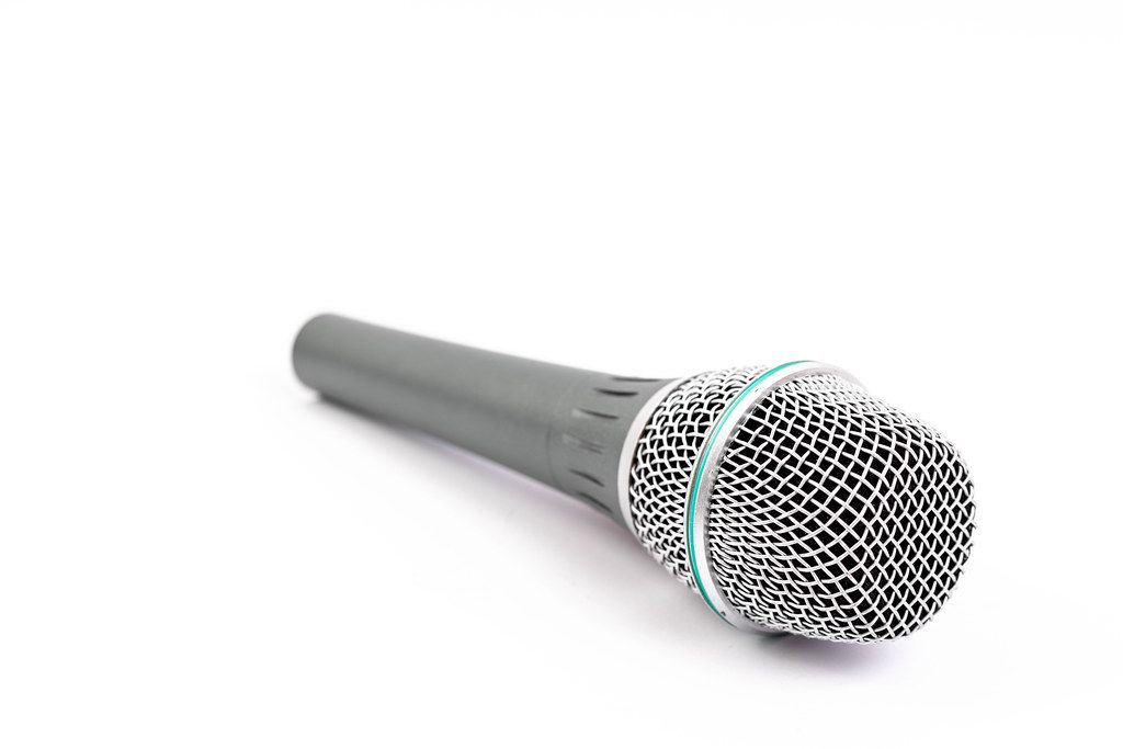 Grey Vocal Microphone above white background with copy space