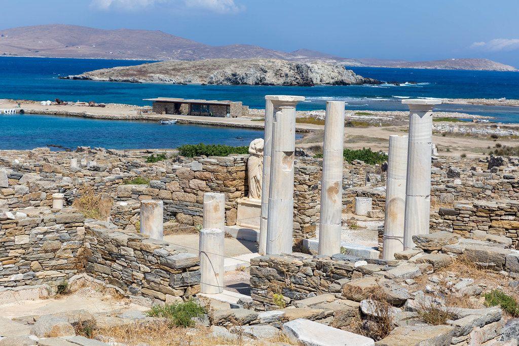 Griechische Säulen des Hauses der Kleopatra auf Delos. Unbewohnte Inseln im Hintergrund