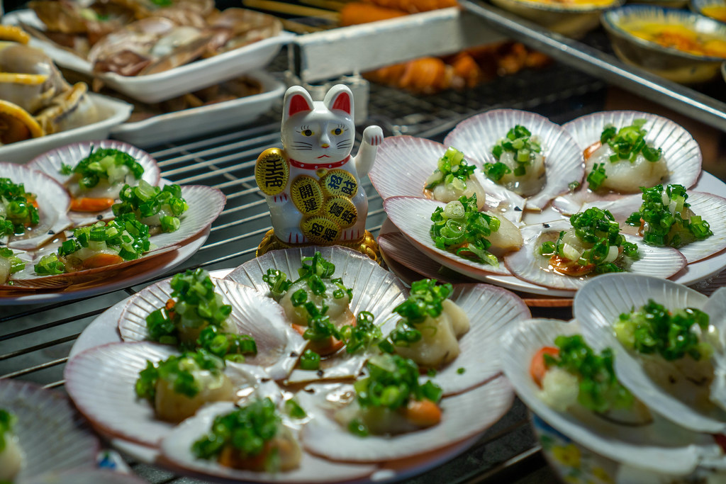 Grilled Scallops with Spring Onion on a Barbecue Grill with a Small Waving Cat as Decoration at a Nightmarket in Vietnam