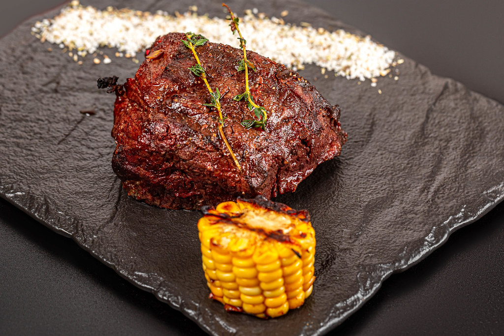 Grilled steak filet mignon served with grilled corn and thyme