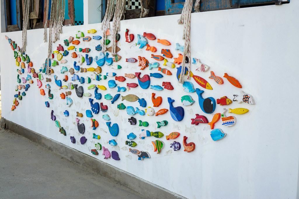 Großer Fisch als Kunstwerk an einer Hauswand mit vielen kleinen bunten Fischen und Walen an einem öffentlichen Strand in Da Nang, Vietnam