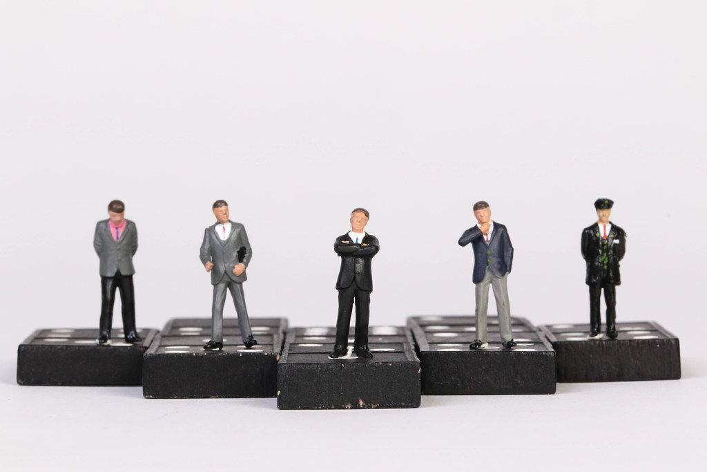 Group of businessman people standing on dominoes with white background