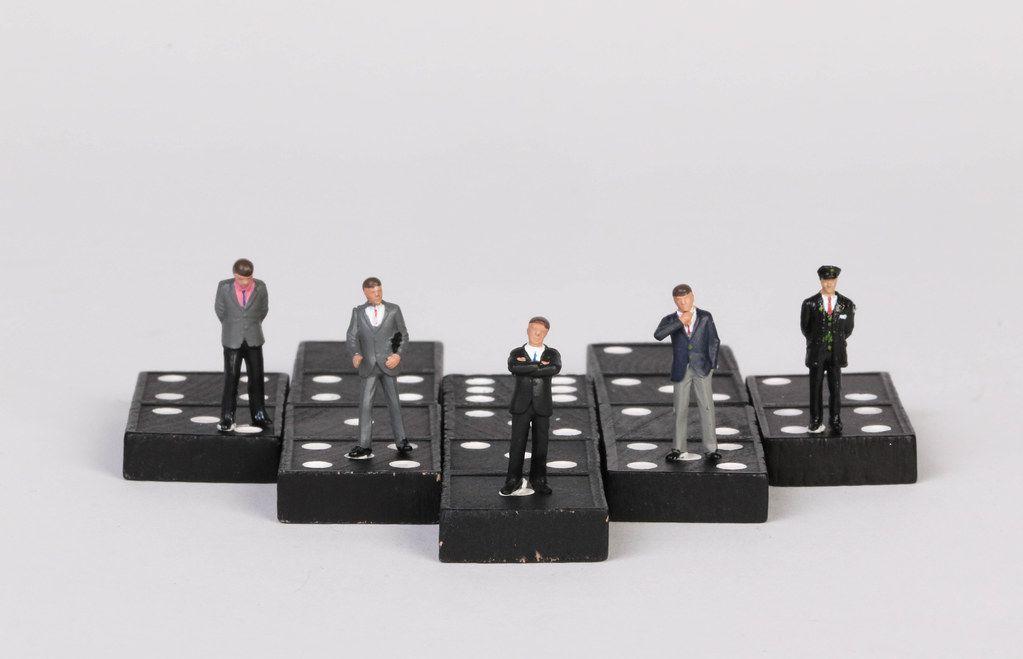 Group of businessman people standing on dominoes