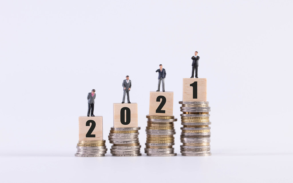 Group of businessman, stack of coins and wooden cubes with 2021 text