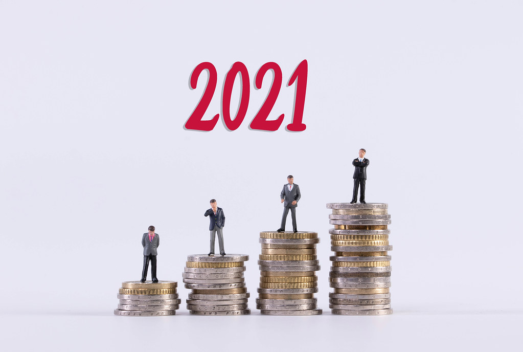 Group of businessman standing on stack of coins with red 2021 text