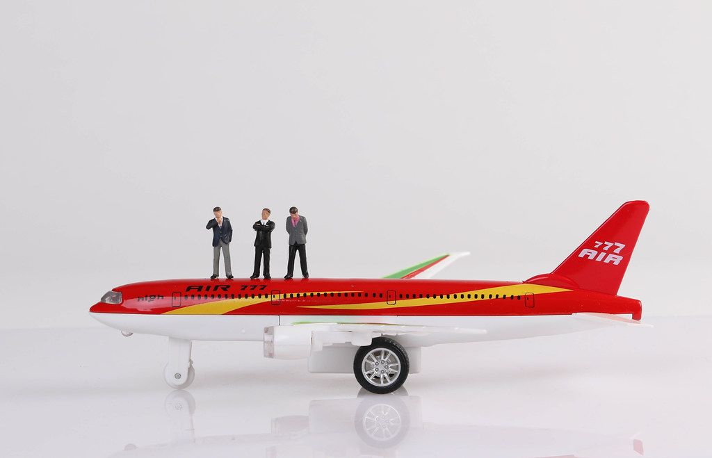 Group of businessman standing on toy airplane