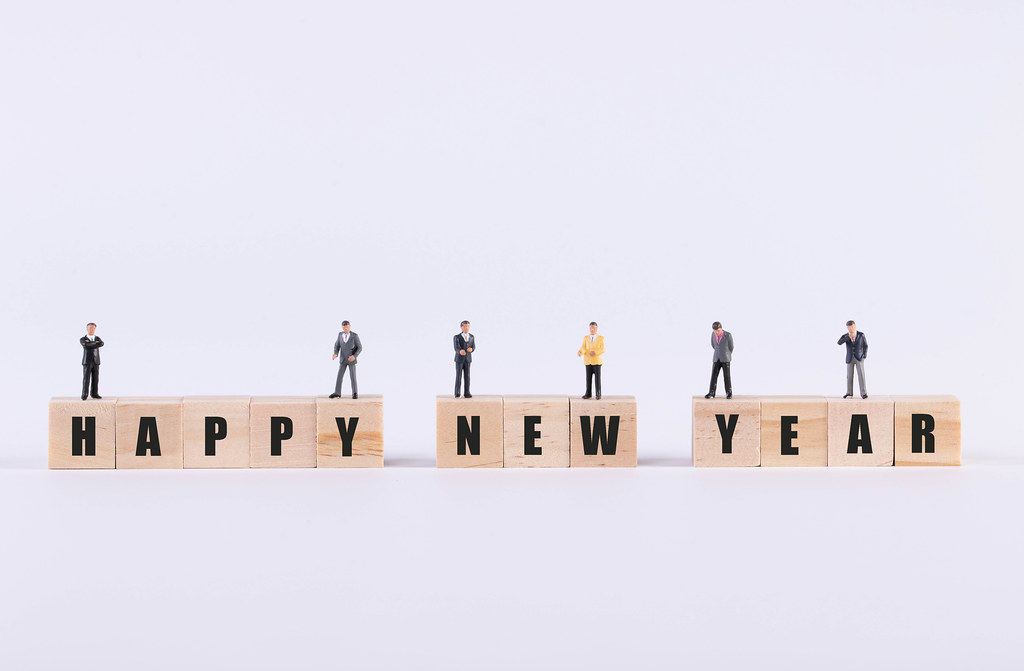 Group of businessman standing on wooden cubes with Happy New Year text