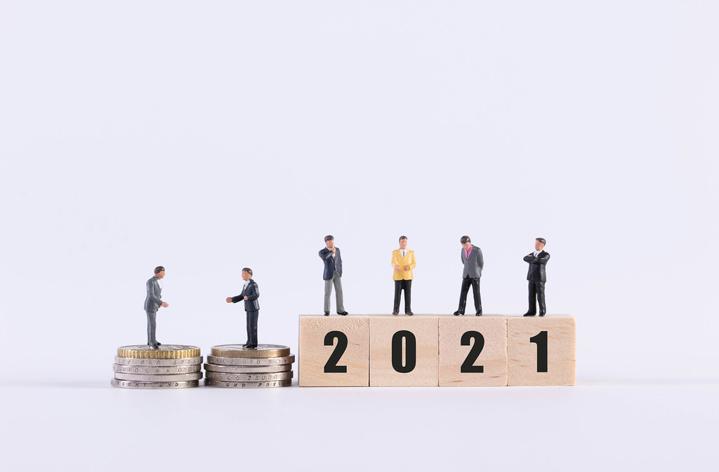 Group of businessman with coins and wooden cubes with 2021 text