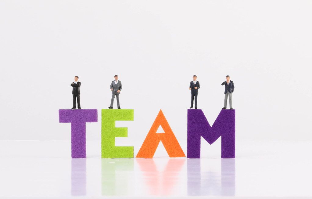 Group of miniature businessman with Team text on white background