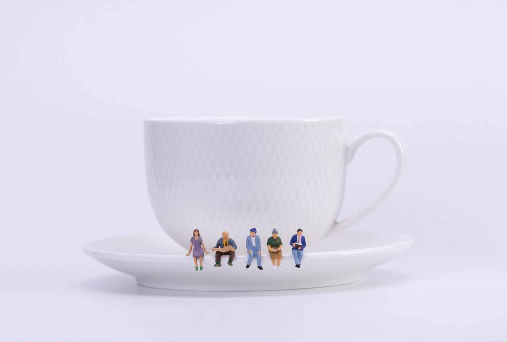 Group of miniature people figures sitting, waiting and reading newspaper and book on white plate of cup of hot coffee