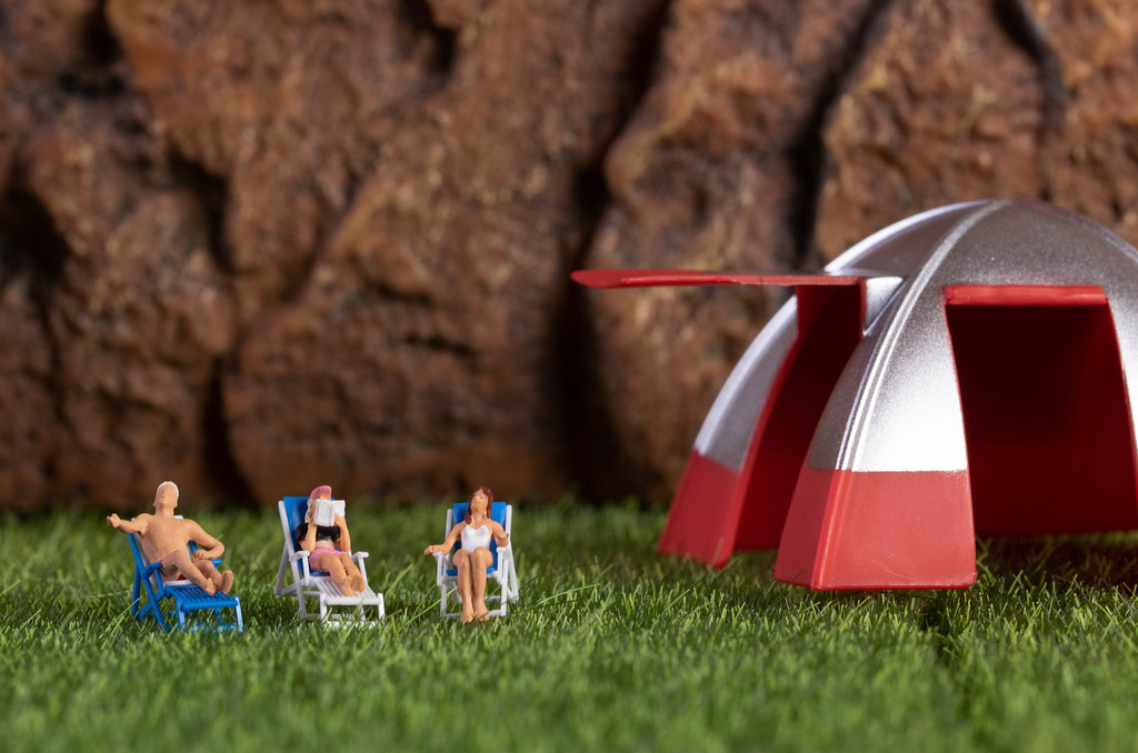 Group of miniature people relaxing in deckchairs in the nature
