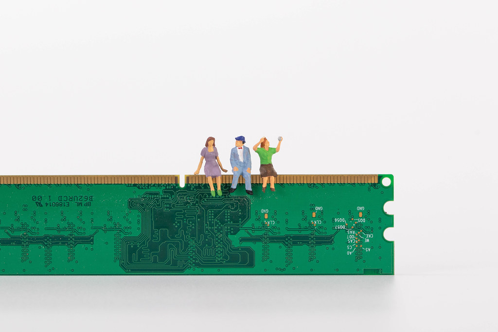 Group of miniature people sitting on a computer chip