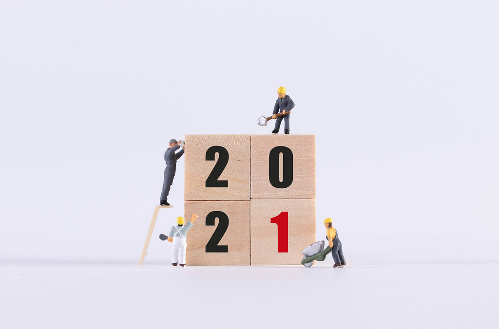 Group of miniature workers and wooden cubes with 2021 text