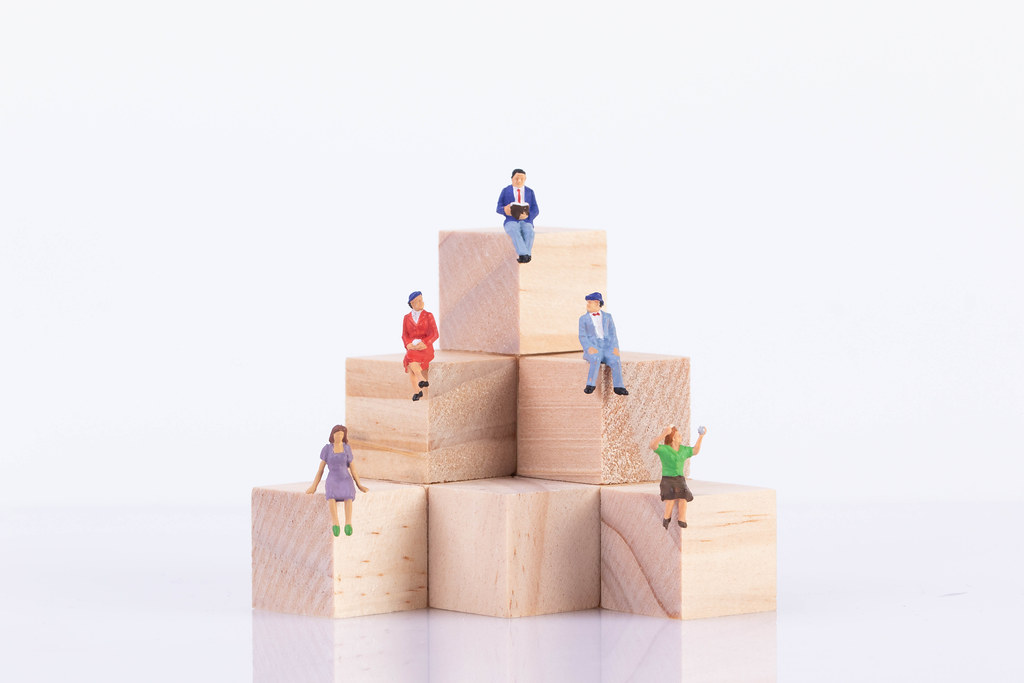 Group of people sitting on wooden blocks
