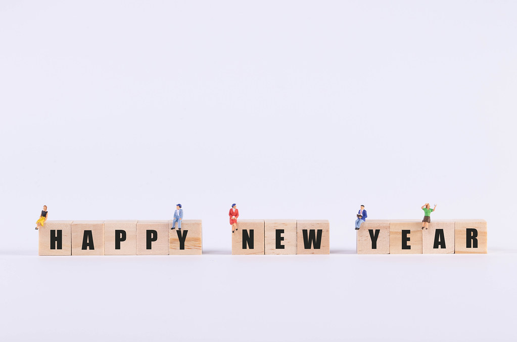 Group of people sitting on wooden cubes with Happy New Year text