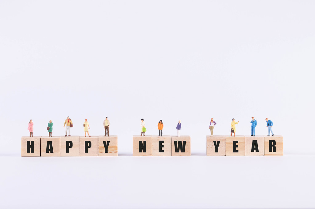 Group of people standing on wooden cubes with Happy New Year text