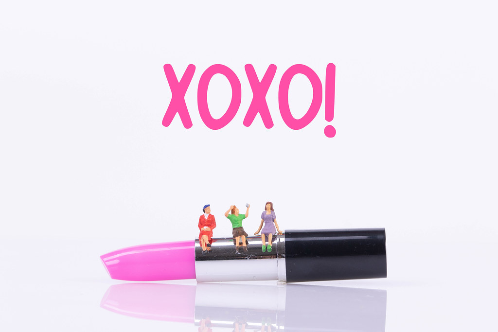 Group of womans sitting on make up with XOXO text