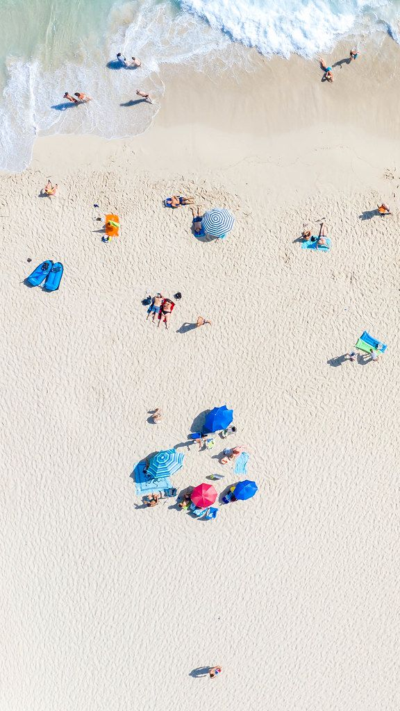 Groups, families and couples lying on the beach of Cala Mesquida in Mallorca. Drone photo