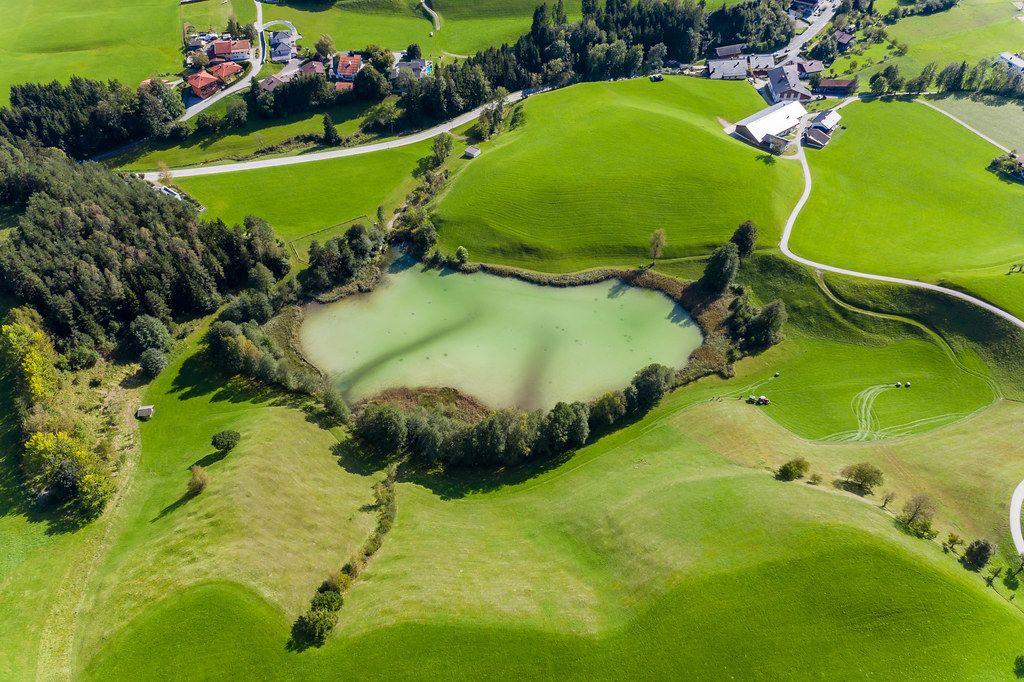 Grüne Hügel, Bäume und kleiner Frauensee mit hellgrünem Wasser bei Kramsach, Tirol. Luftbild