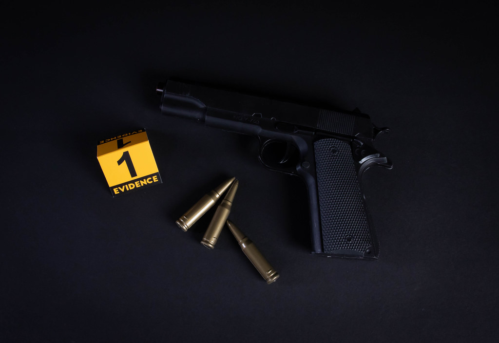 Gun and evidence marker on black background