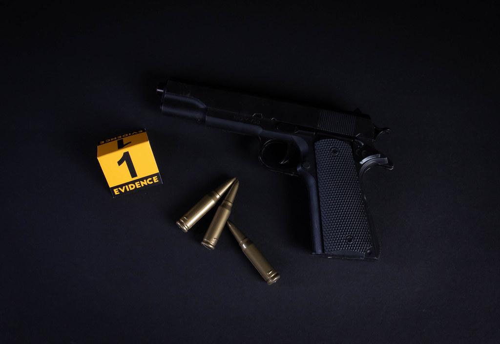 Gun and evidence marker on black background