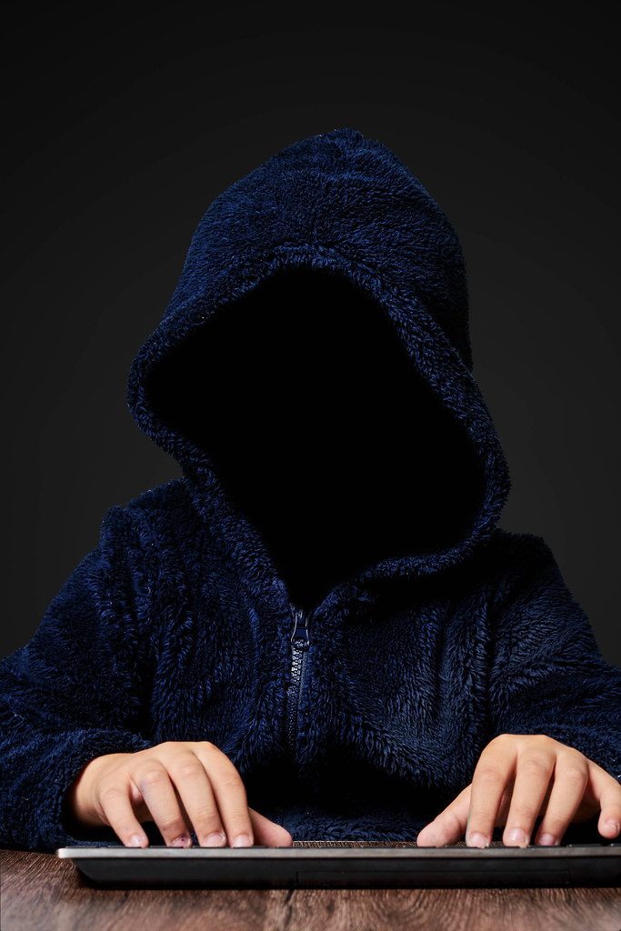 Hacker working in the dark. Faceless hooded anonymous computer hacker