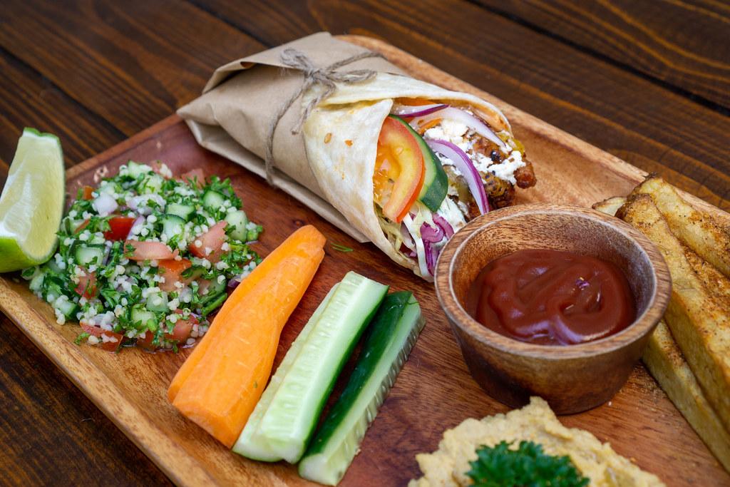Hähnchen Döner Durum Rolle mit Pommes Frites, Quinoa Salat, Gemüse und Hummus Dip als Mittagsmenü auf einem Holzteller in einem Restaurant