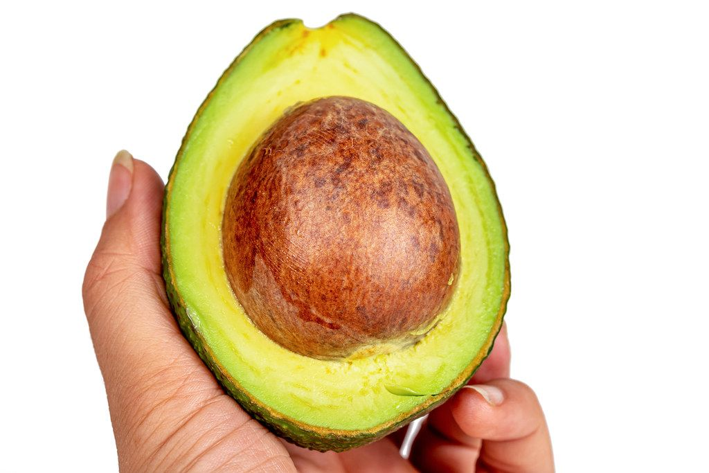 Half a fresh avocado in a woman