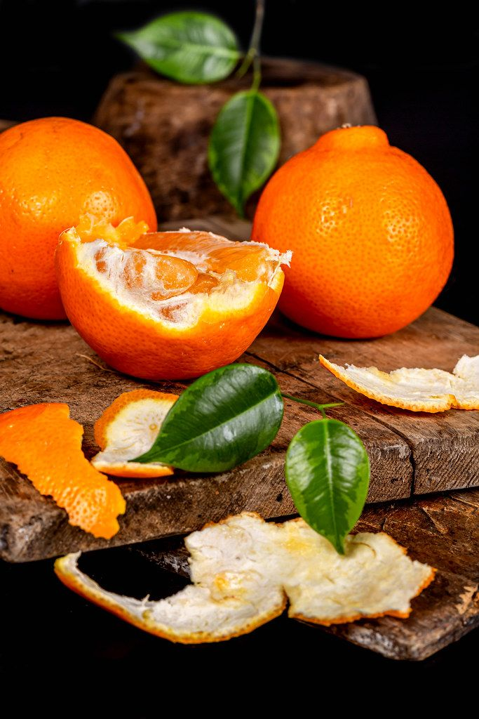 Half and whole fresh tangerines on old kitchen boards