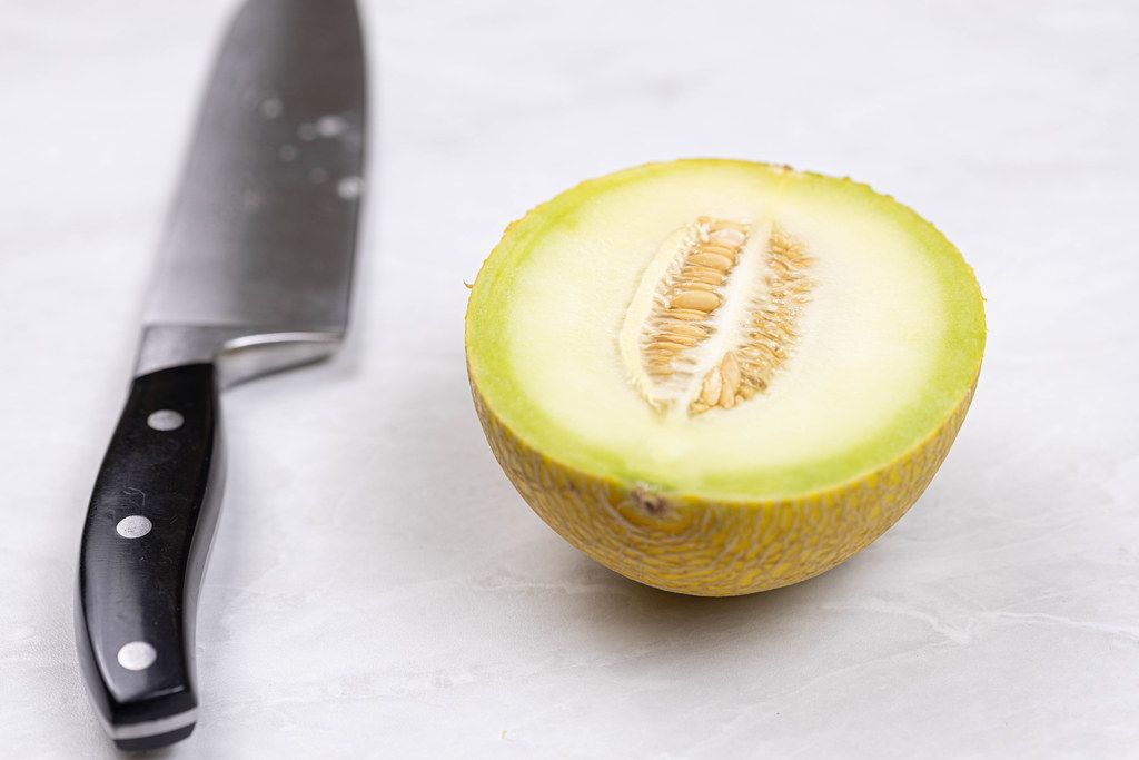 Half Mini Melon on the grey table with knife