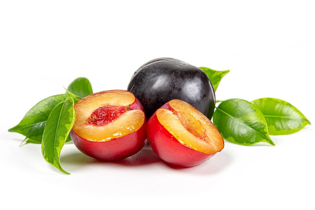 Halves and whole plums on a white background with green leaves