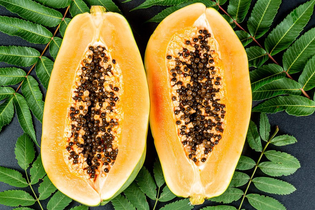 Halves of ripe papaya on a black background with leaves, top view