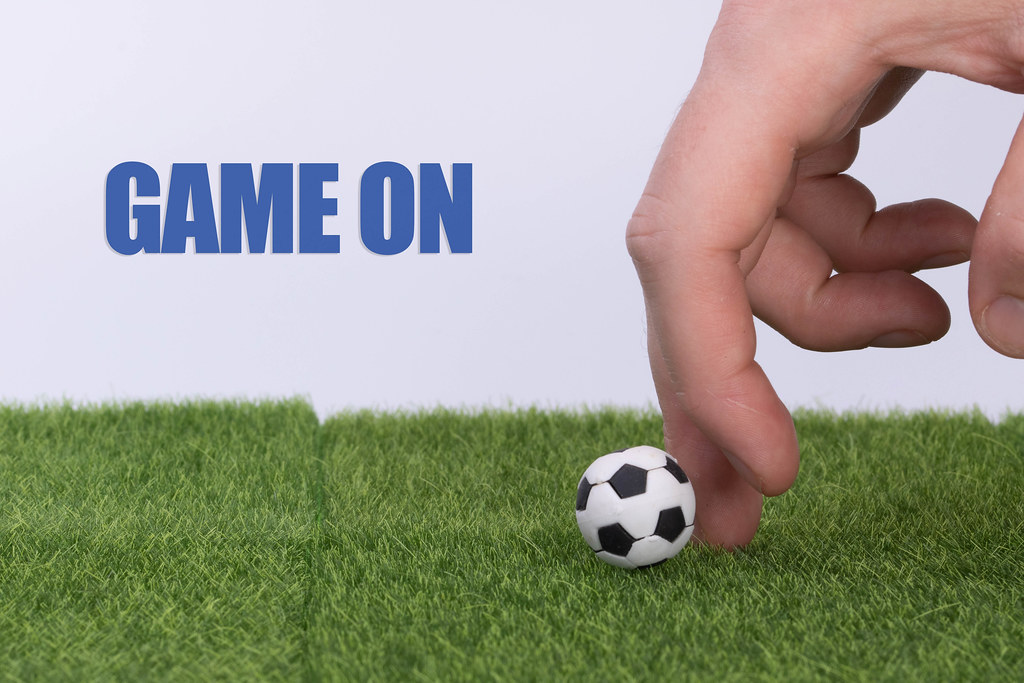 Hand and soccer ball with Game on text