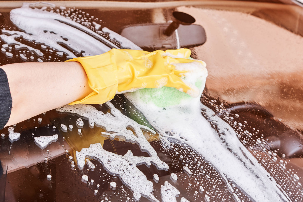 Hand car wash - washing windshield with sponge
